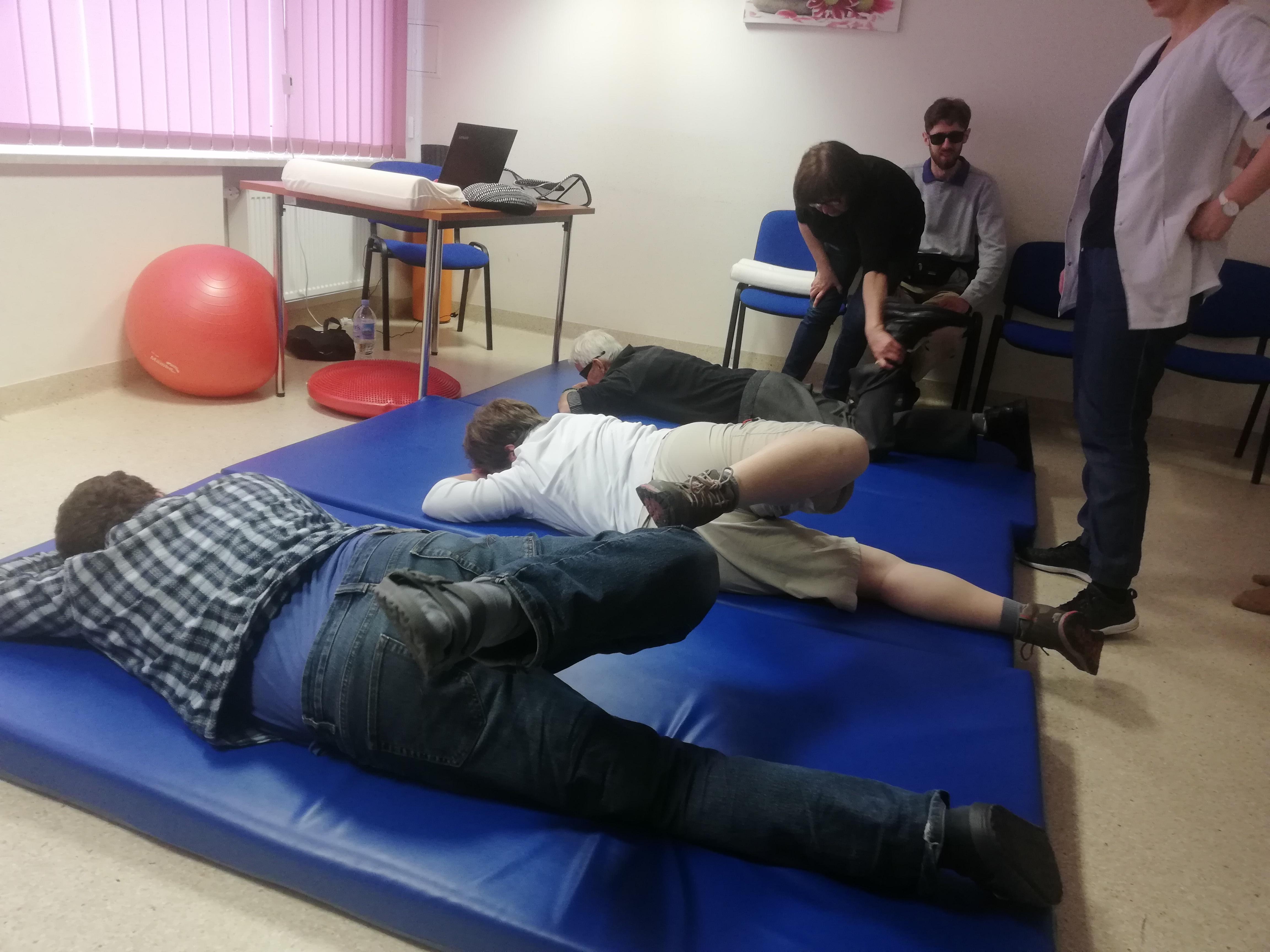 Dwie osoby ćwiczą synchronicznie leżąc na brzuchu, na niebieskich materacach. Są widoczne podczas odchylania w lewo zgiętej w kolanie prawej kończyny. Ubrane są odpowiednio w koszulę w kratkę i biały T - shirt. W lewym rogu tuż obok biurka leży duża czerwona piłka.