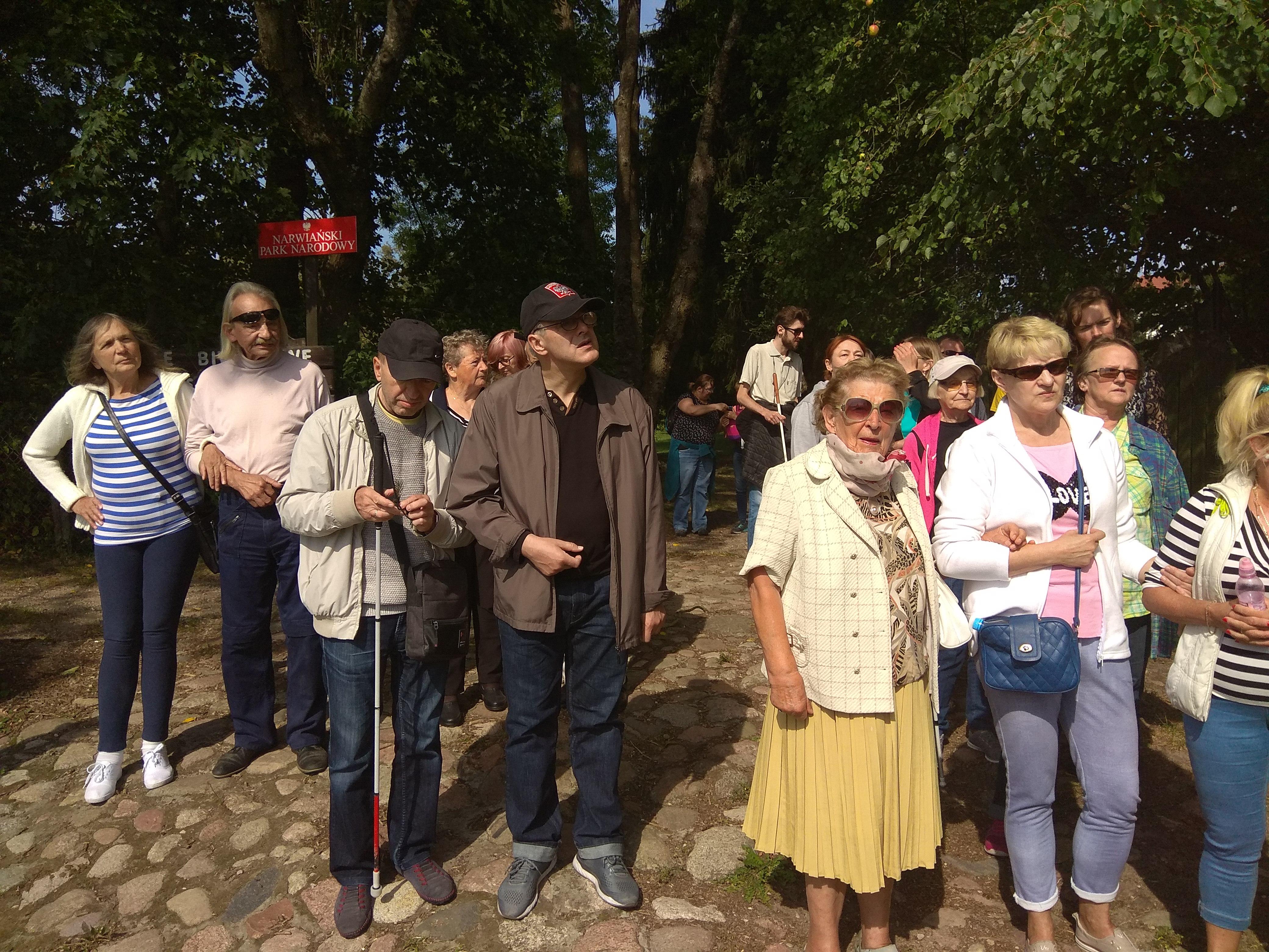 Spora grupa osób w różnym wieku stojąca na dworze to nasi zjazdowicze gotowi do wymarszu. Stoją na charakterystycznym podłożu z białymi kamieniami.