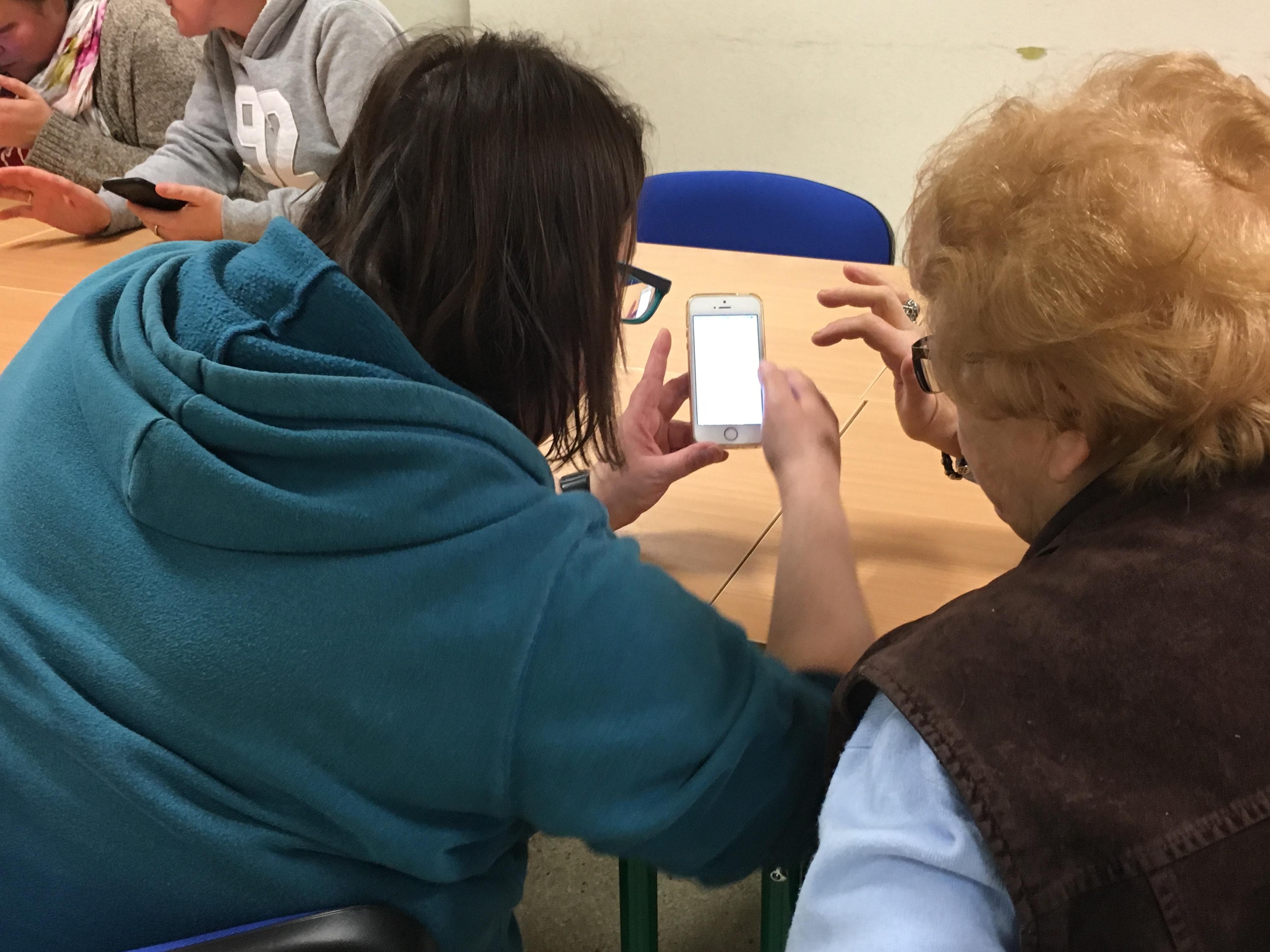 Brunetka w okularach i niebieskiej bluzie z kapturem trzyma dwiema rękami smartfon pokazując coś na nim siedzącej obok blondynce w krótkich włosach, która trzyma dłoń blisko smartfona. Panie sfotografowane od tyłu.