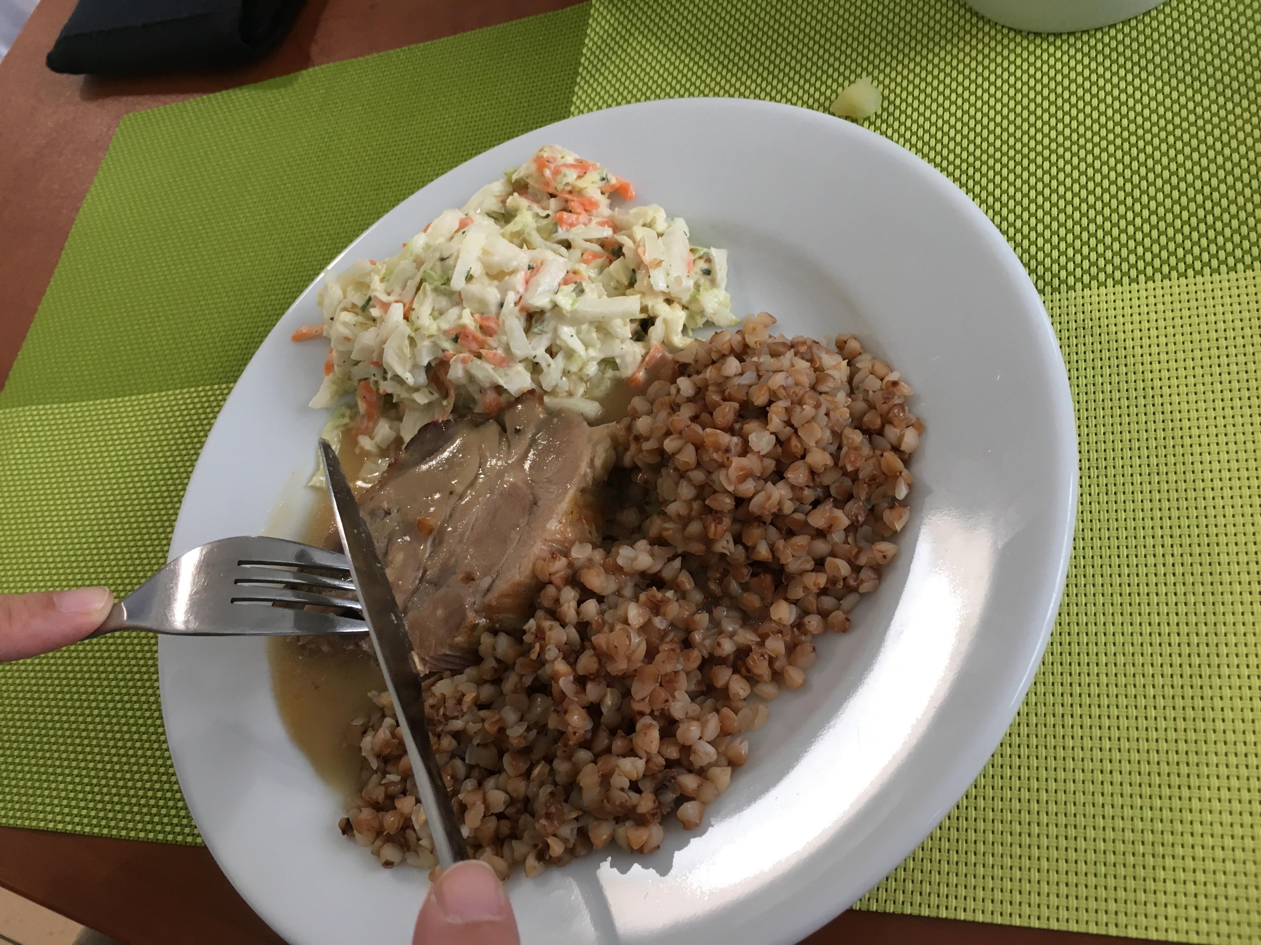 Smacznie i zdrowo – zdjęcie przedstawia biały talerz stojący na zielonej podstawce, a na nim kasza, porcja mięsa i surówki.