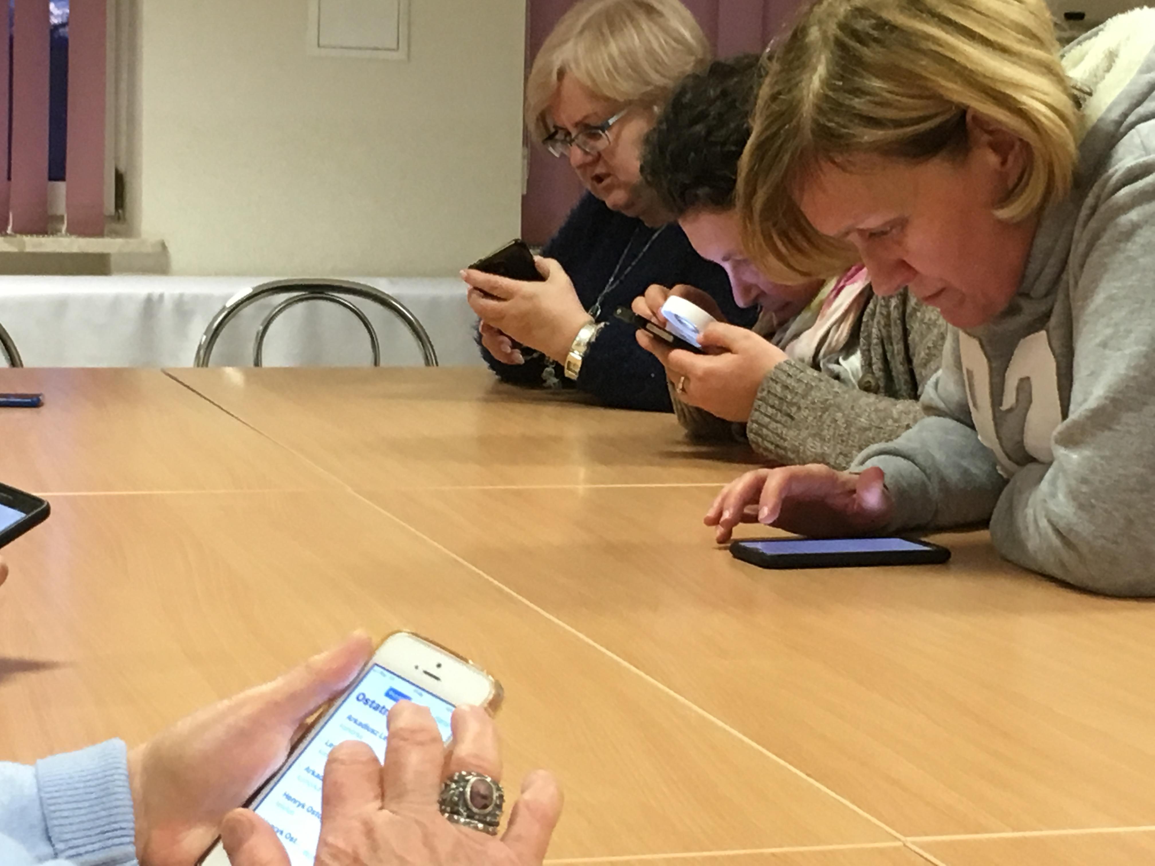 Dwie uczestniczki zjazdu, jedna z nich w okularach, siedzące przy stole pochylone nad smartfonami, które trzymają w dłoniach.