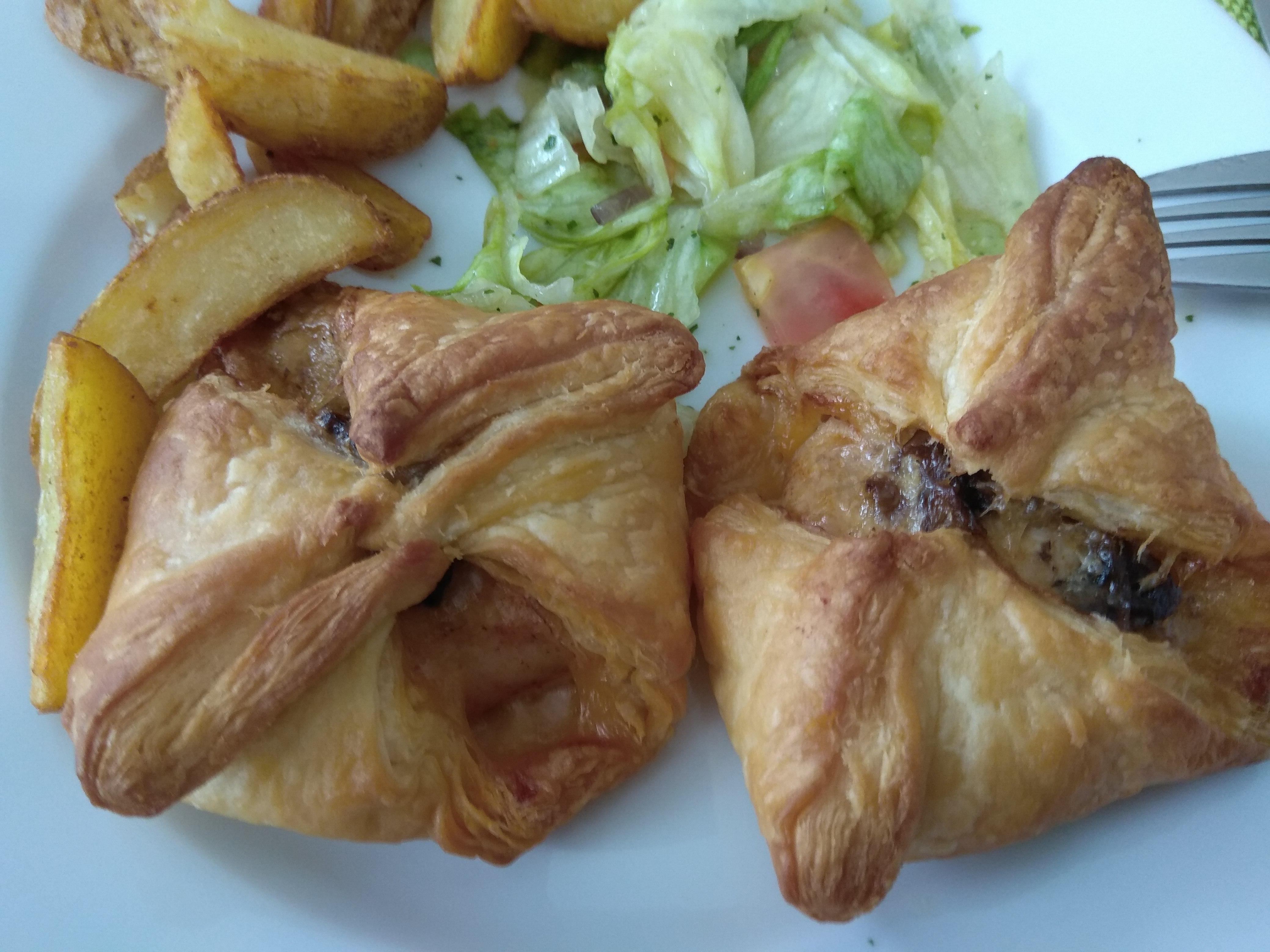 Apetycznie, estetycznie – zbliżenie na talerz z dwoma krokietami mięsnymi w  cieście francuskim i bukietem sałat.