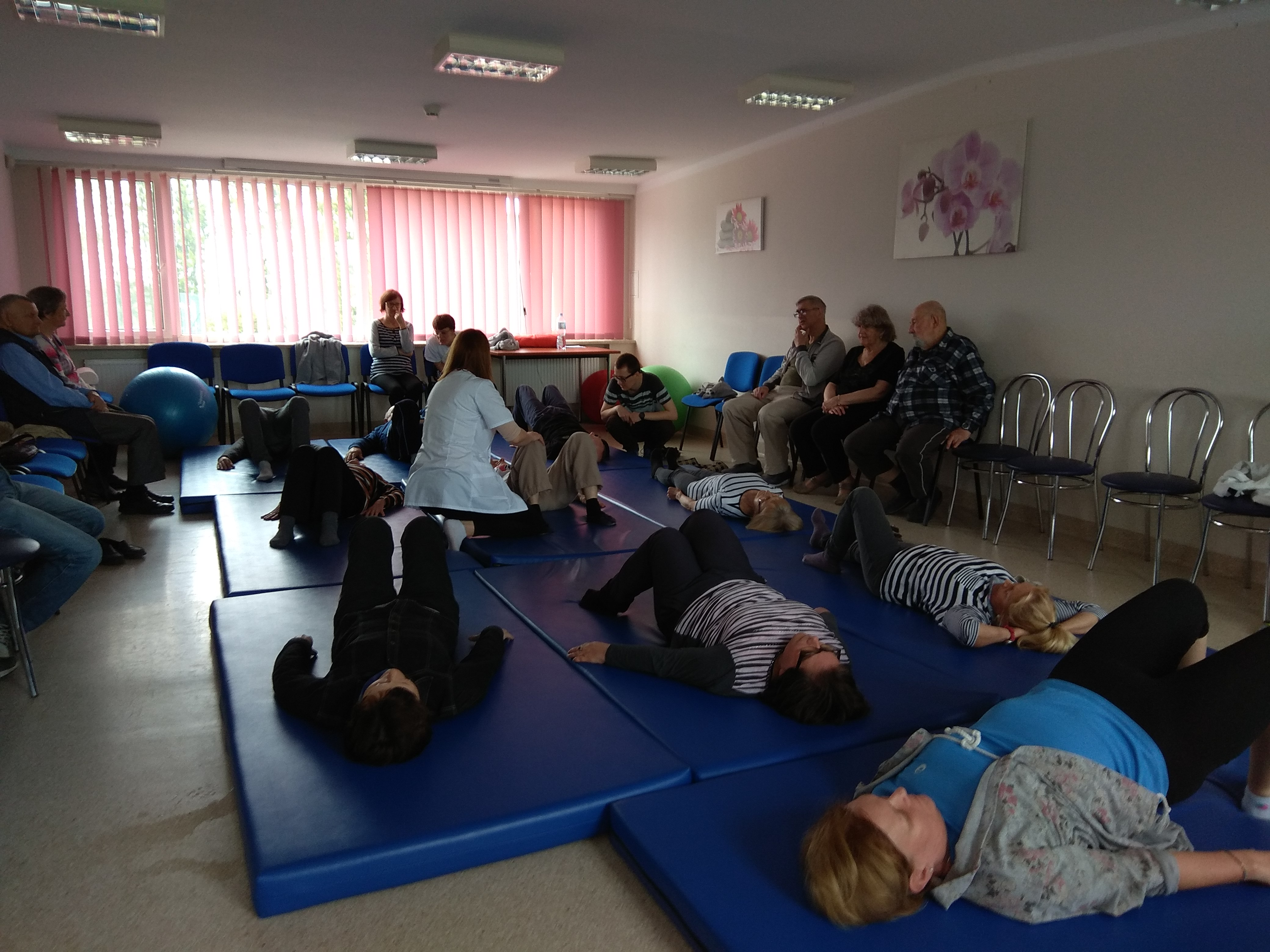 Podczas ćwiczeń – kilkoro uczestników wykonuje ćwiczenia leżąc na plecach, na niebieskich materacach. Wszyscy opierają swe stopy na materacu, a kolana mają zgięte. Pomiędzy nimi przy jednej z osób siedzi fizjoterapeutka opierając swe dłonie na jej kolanach, nadając właściwy przebieg ćwiczenia. Trzy osoby leżące blisko siebie ubrane są w biało – czarne podkoszulki w paski.