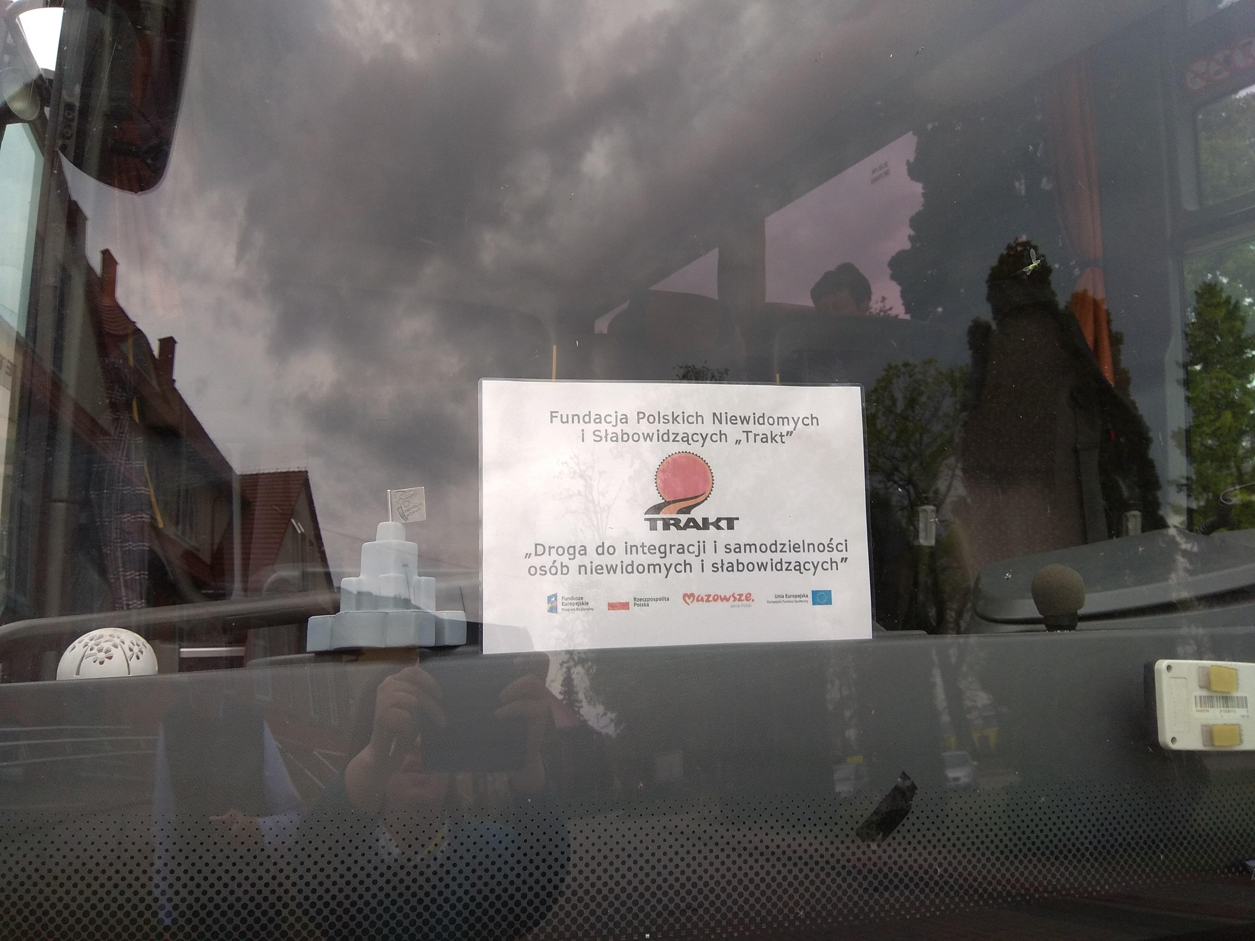 Przednia szyba autokaru z tablicą z logo Fundacji TRAKT i informacjami o projekcie, na której widać odbicie otaczających go budynków.