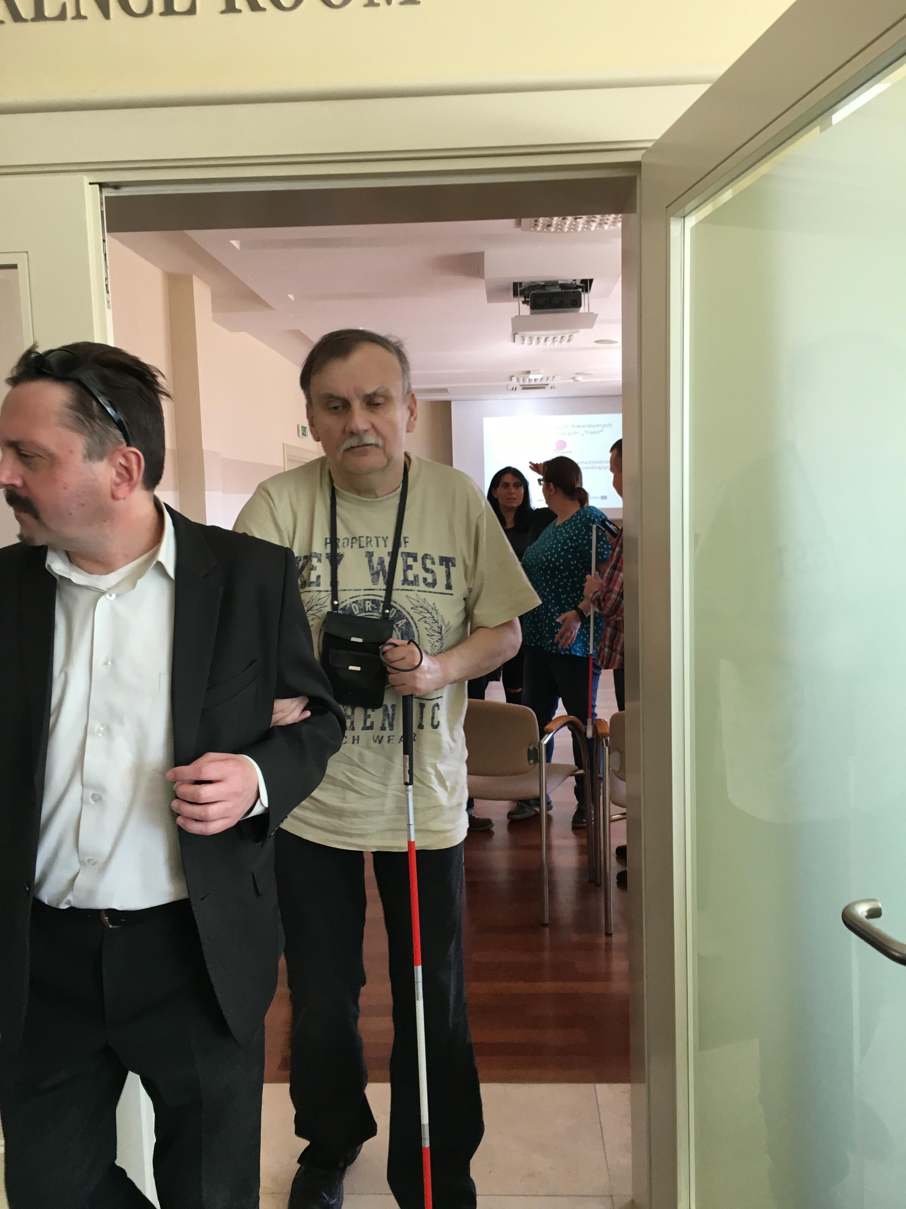 Dwaj panowie wychodzący z sali. Jeden z nich w czarnym garniturze i białej koszuli. Drugi w przejściu do hallu, w białej podkoszulce, trzyma w ręku laskę.