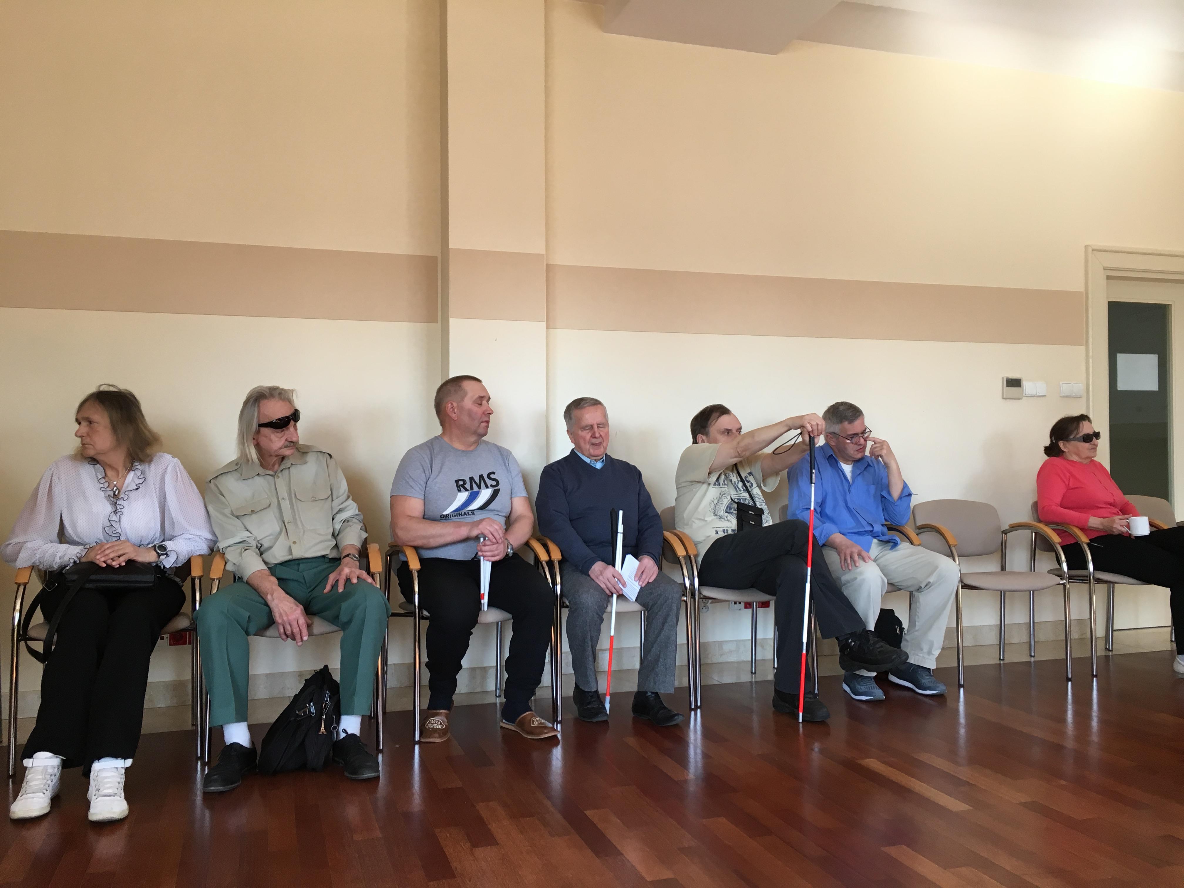 Uczestnicy siedzący na krzesłach ustawionych wzdłuż ściany. Jeden z nich trzyma ręce wysoko oparte na lasce.