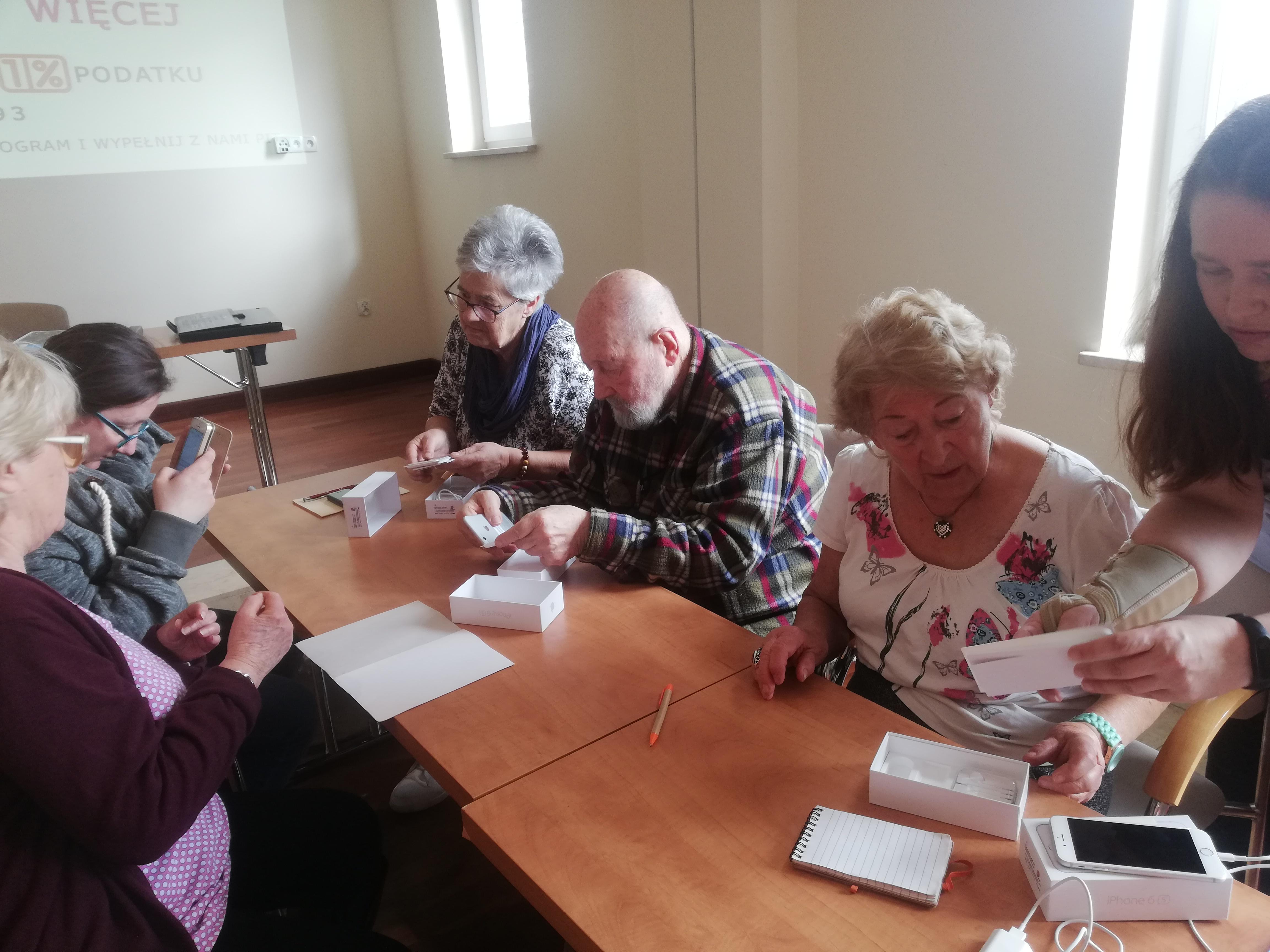 Pięć osób siedzących przy dwóch połączonych ze sobą stołach podczas rozpakowywania smartfonów. Z prawej strony widoczna twarz stojącej kobiety, która pomaga blondynce w białej, wzorzystej bluzce i krótkich, lekko kręconych blond włosach.