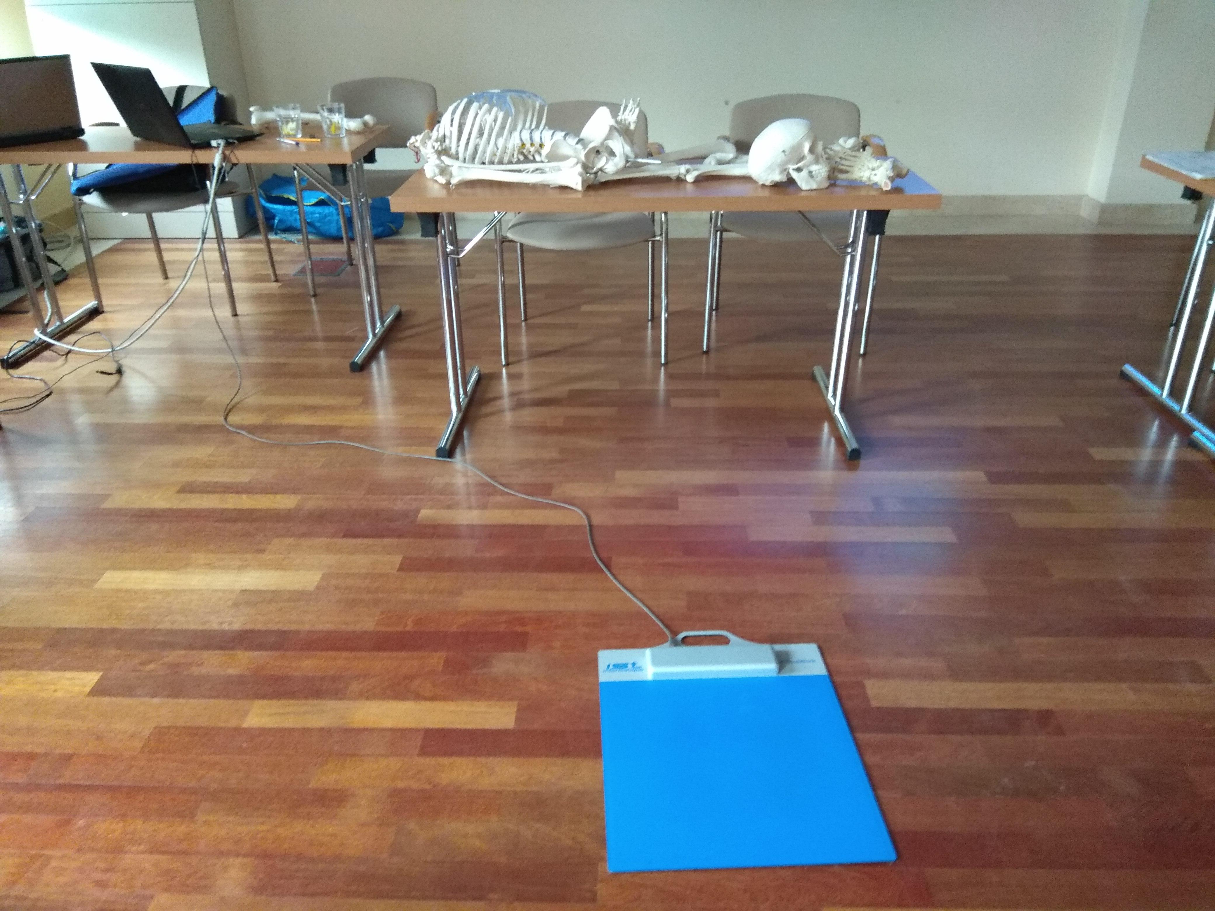 Sala z jasnobrązowymi panelami, na nich leży podoskop, to płaski, niebieski kwadrat podpięty długim przewodem do gniazda. Na prostokątnym stole leży model szkieletu człowieka.