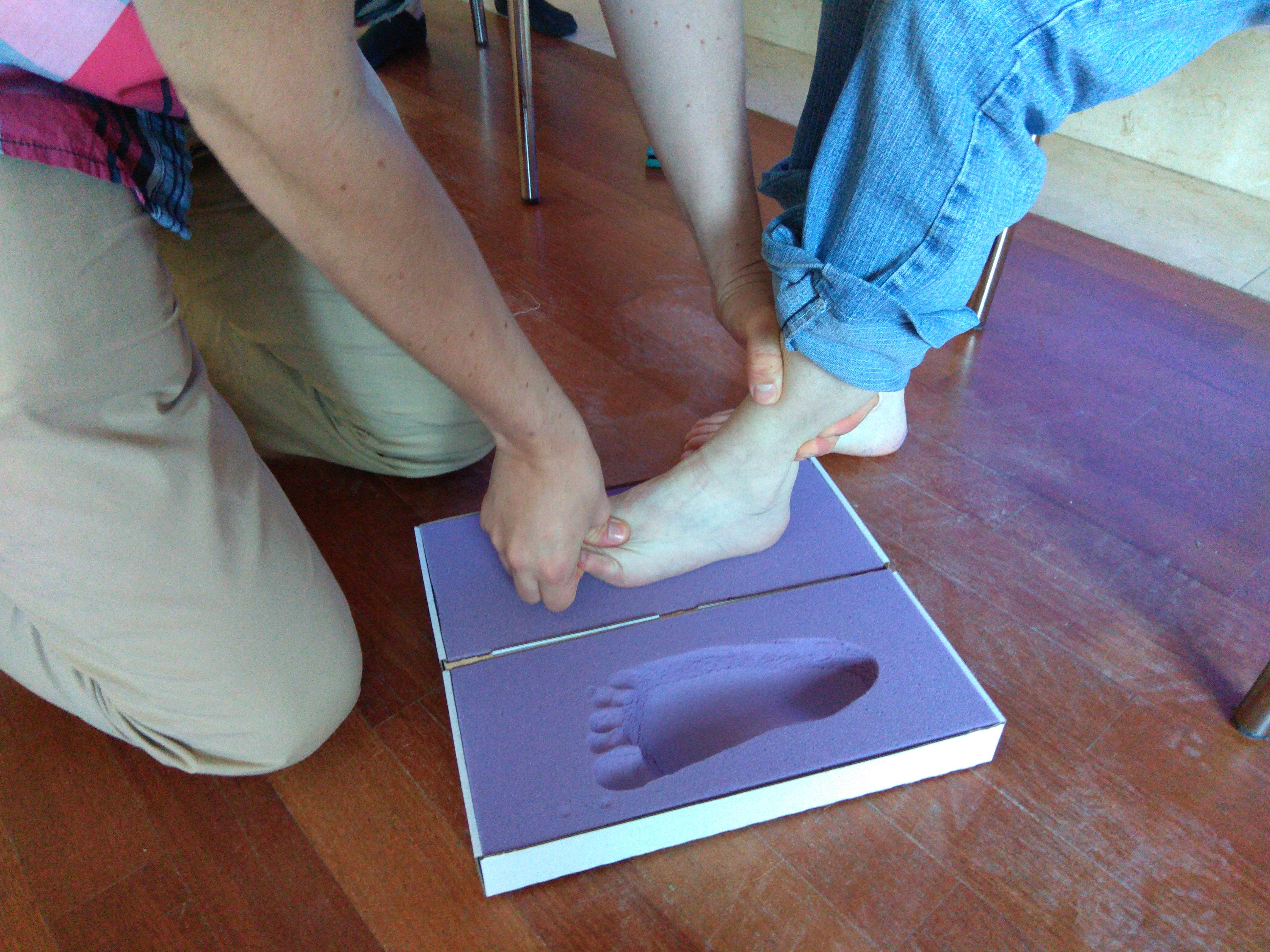 W zbliżeniu goła stopa jednego z uczestników podczas badania. Noga oparta na kwadratowym, fioletowym elemencie, obok widoczny odcisk stopy.
