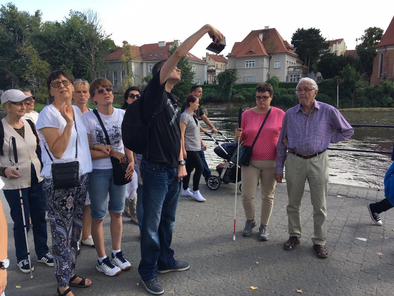 Pamiątkowe selfie – grupa uczestników podczas spaceru nad rzeką