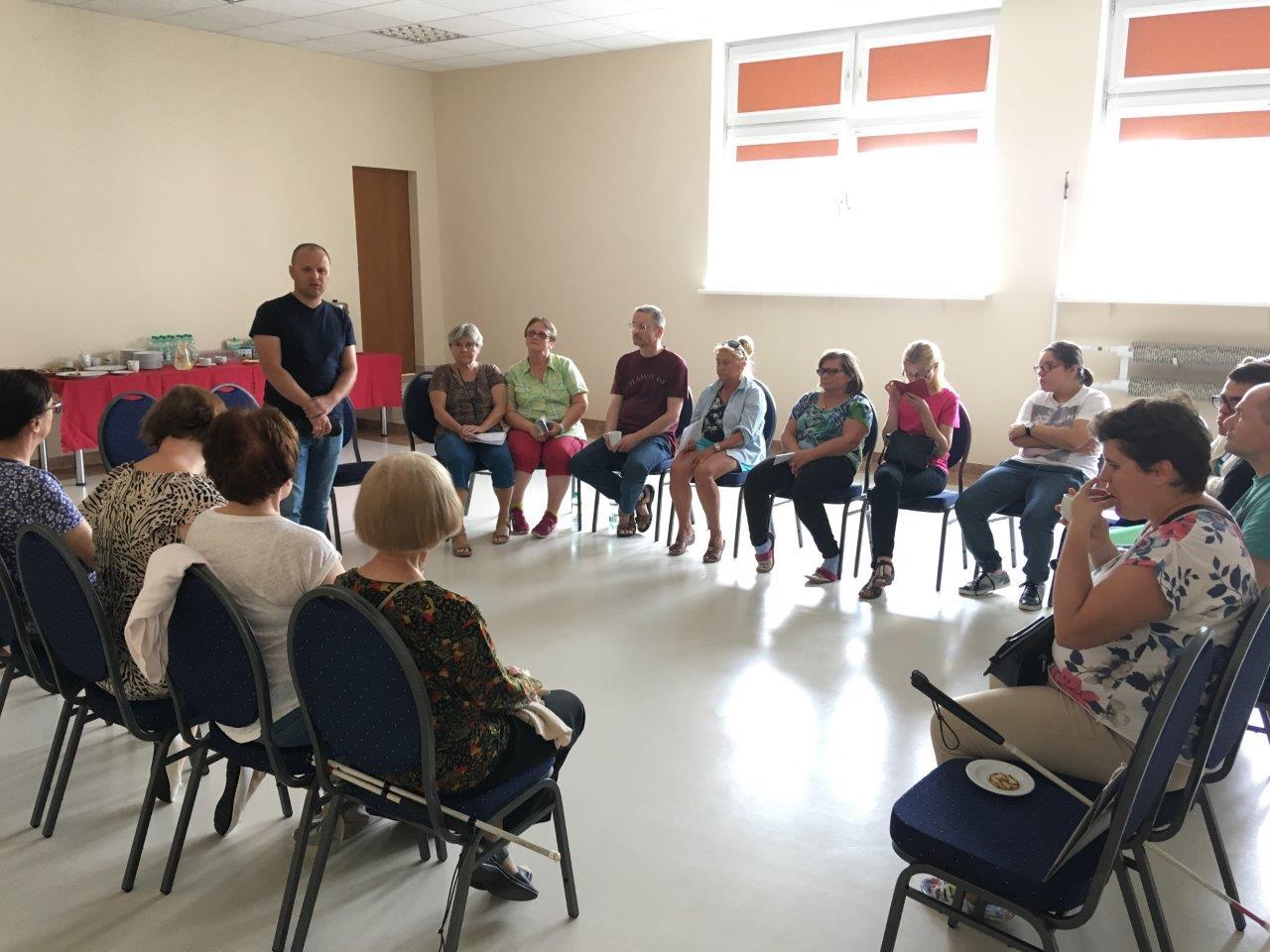 Kursowicze podczas szkolenia ze smartfonów siedzący na krzesłach ustawionych w otwartym okręgu