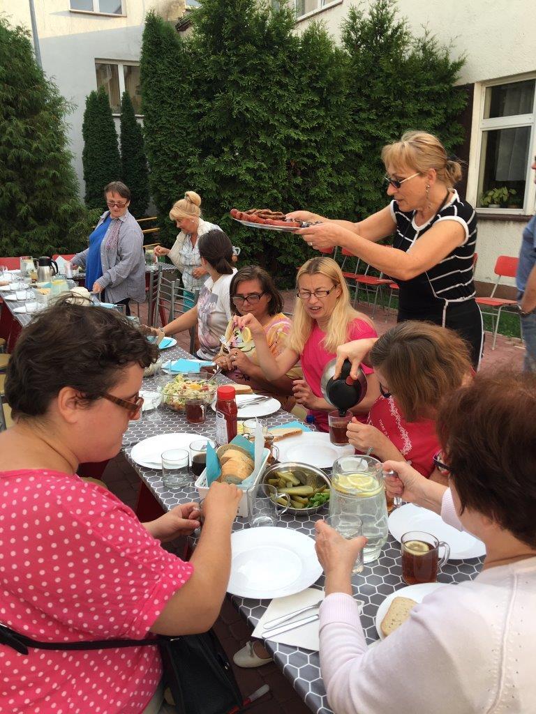 Czas na grillowy posiłek – nasi goście siedzący przy długim, prostokątnym stole na świeżym powietrzu