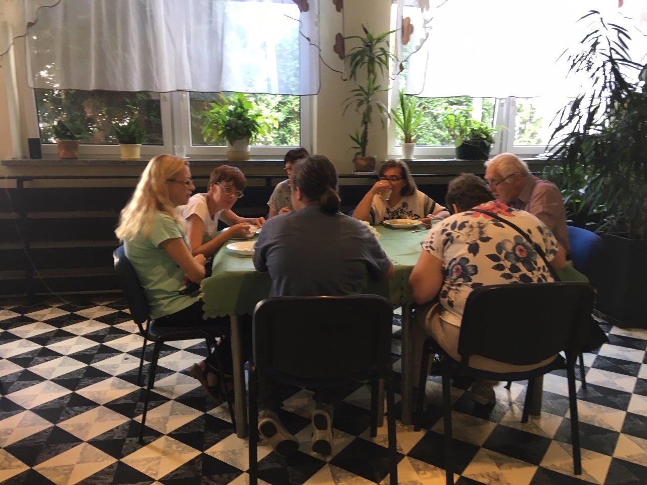 Zjazdowicze podczas posiłku w jadalni z charakterystyczną biało-czarną podłogą w stylu szachownicy, siedzący przy kilkuosobowym stole przy oknie z gładkimi białymi firankami