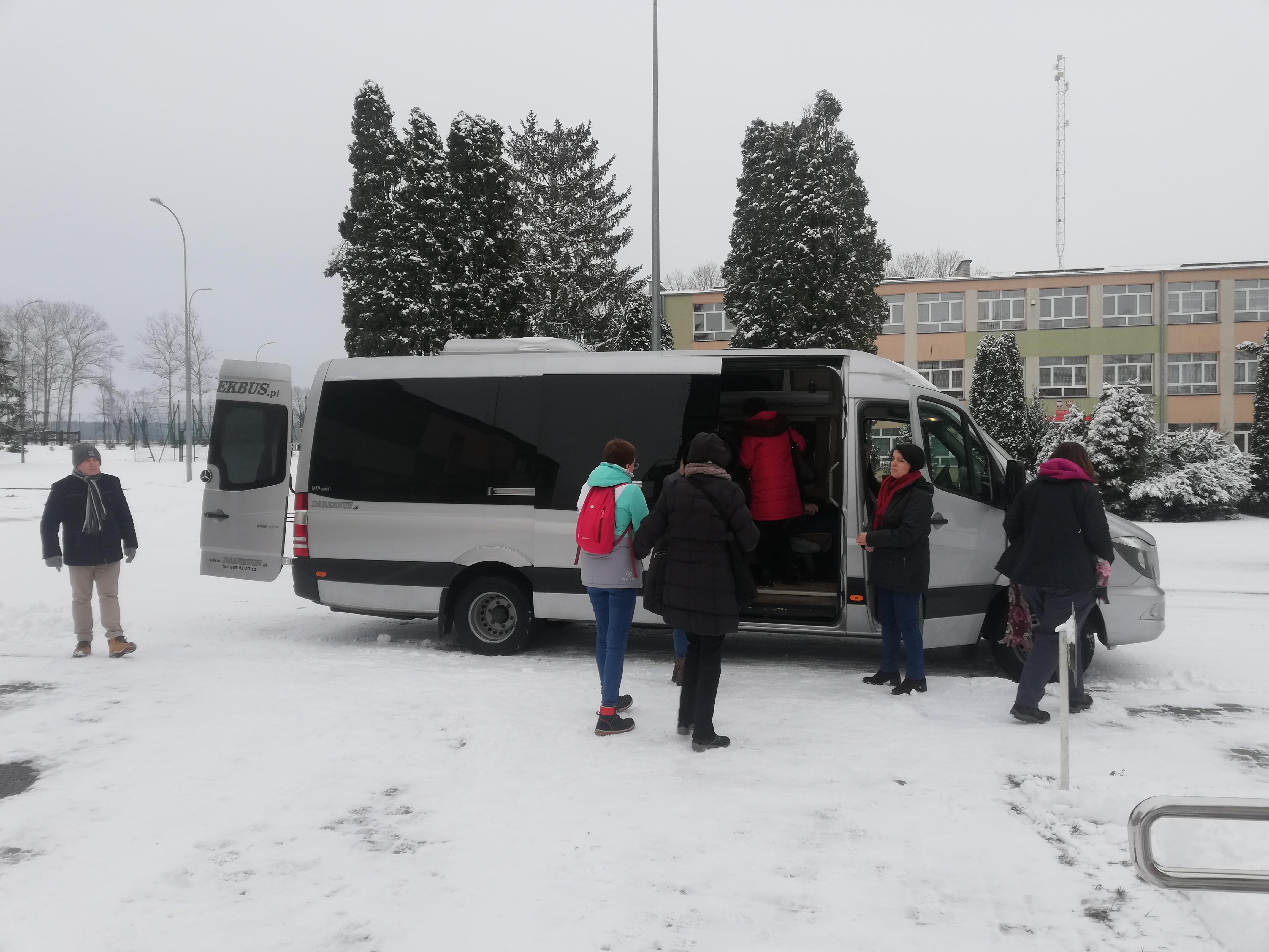 Przed odjazdem –biały bus z otwartymi drzwiami i tylnym bagażnikiem, przy nim kilkoro uczestników na chwilę przed wyjazdem z Krzyżewa, ziemia pokryta śniegiem.
