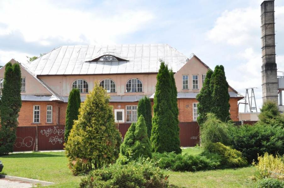 Ośrodek w Krzyżewie – budynek w ceglastym kolorze z czerwoną dachówką i białymi okiennicami w kratę