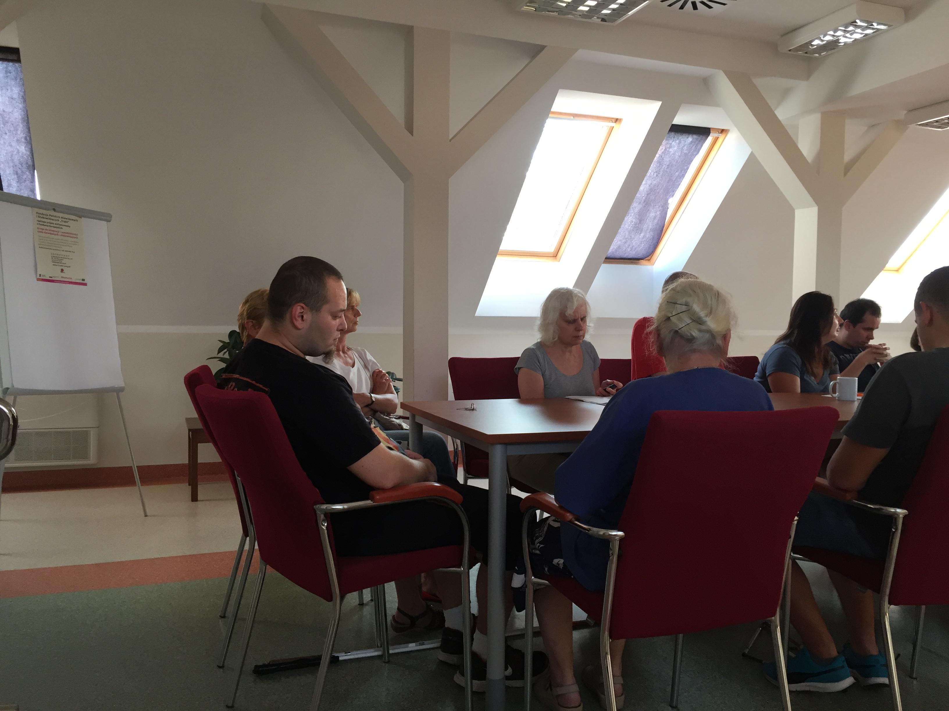 Uczestnicy zjazdu podczas szkolenia w Sali konferencyjnej z widocznym na tablicy plakatem unijnym projektu