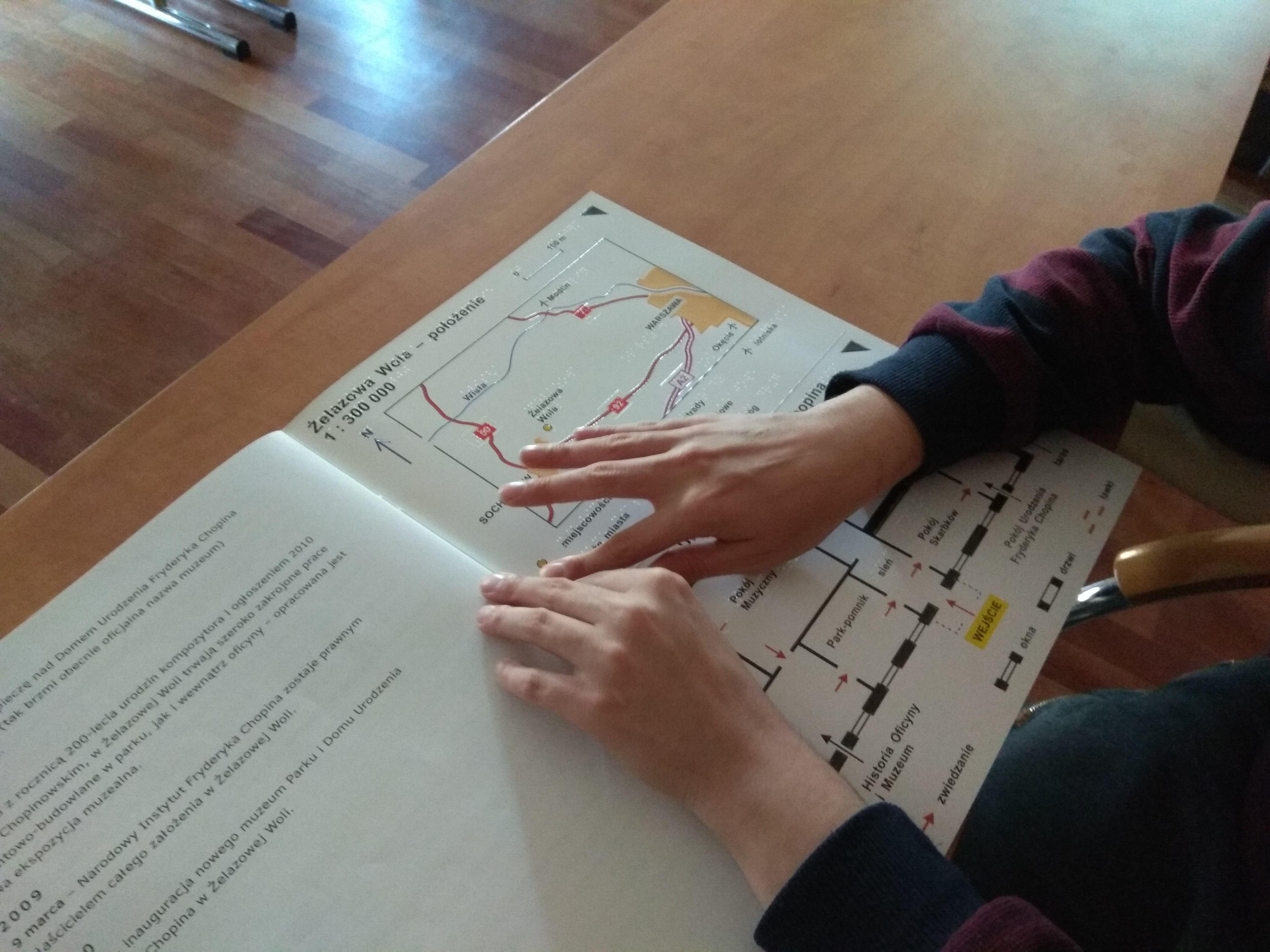 Osoba czytająca dotykiem publikację Żelazowa Wola Miejsce urodzenia Fryderyka Chopina, widoczne dłonie z czarnymi rękawami, wodzące palcami po mapie barwno-wypukłej.