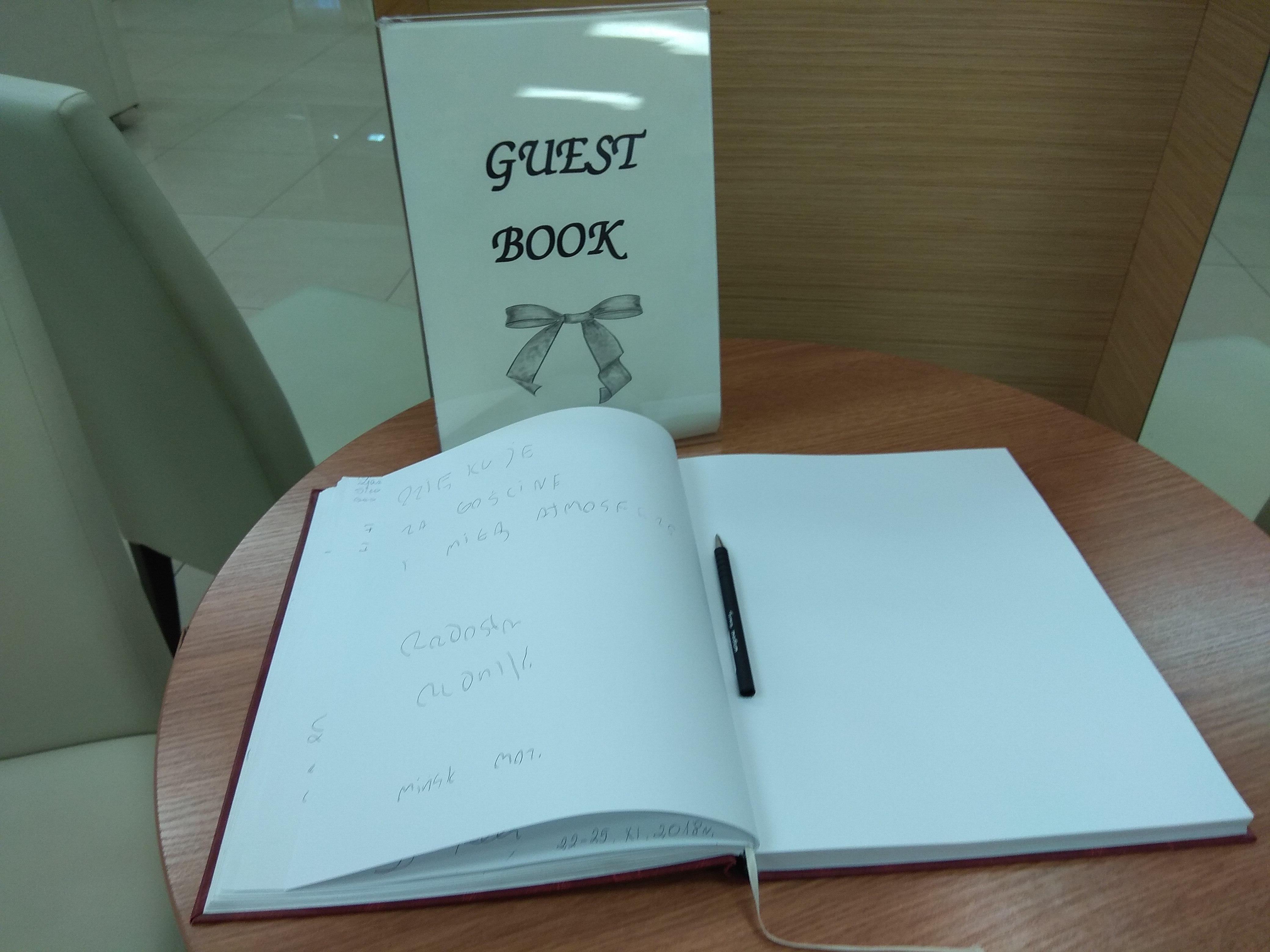 Biała rozłożona księga z czarnym długopisem, a przy niej stojąca tablica z napisem Guest Book.