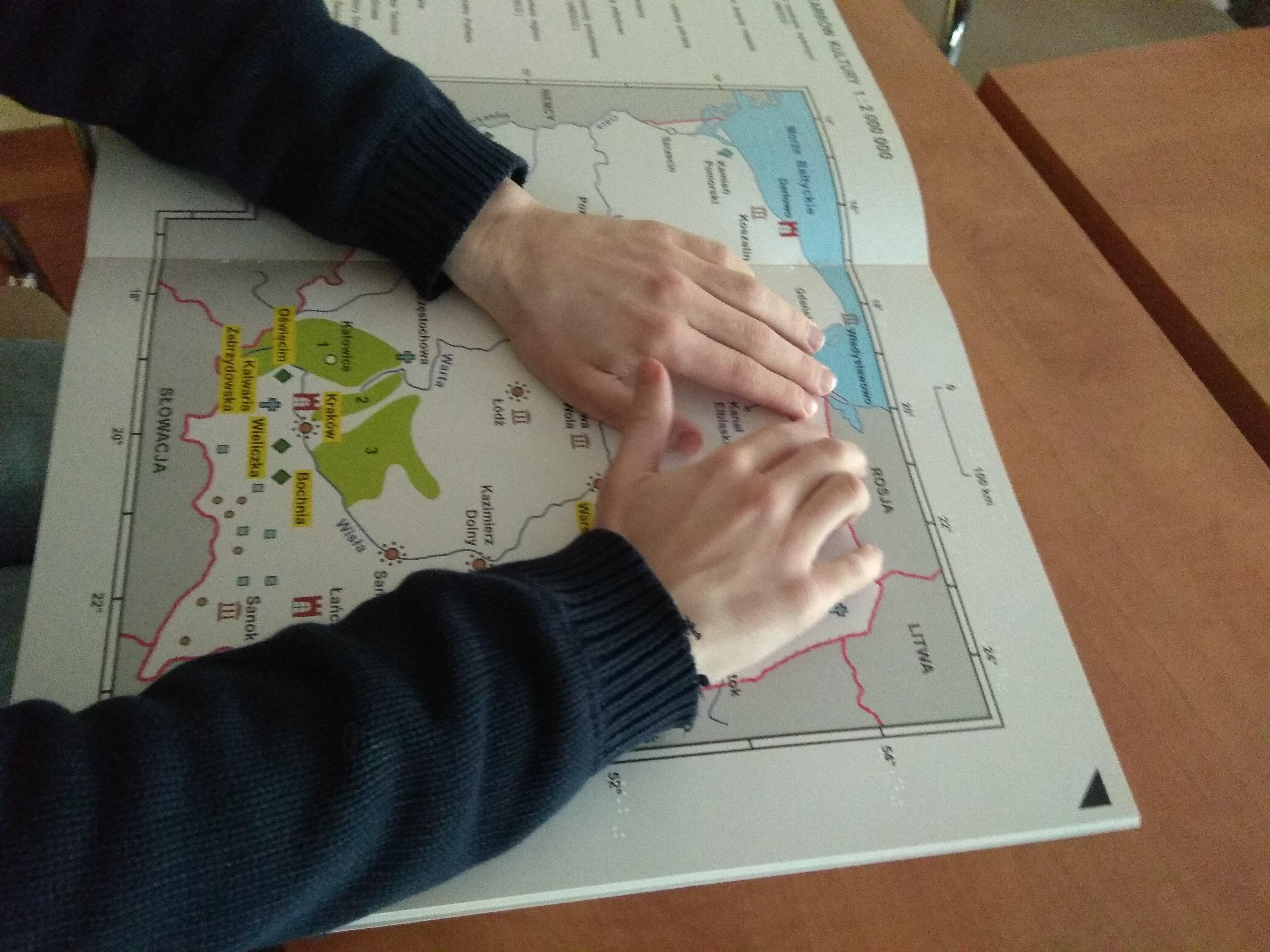 Dłonie uczestnika w czarnych rękawach podczas czytania dotykiem tyflomapy Polski z publikacji Bliżej Skarbów Kultury