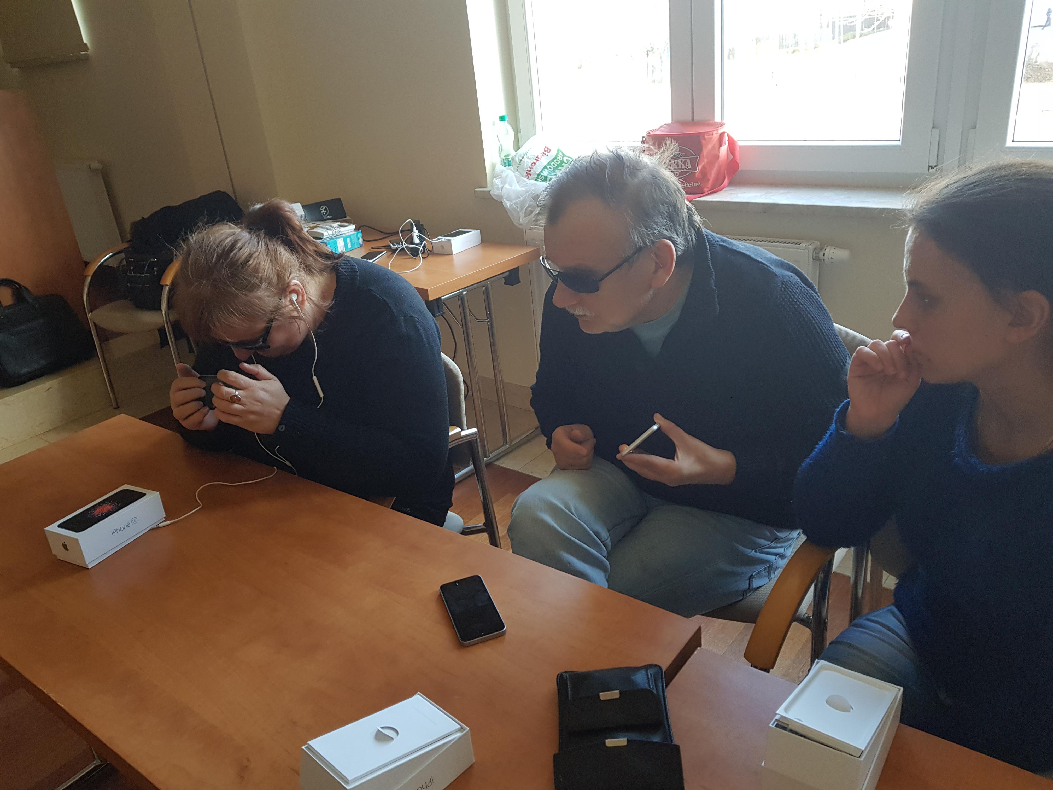 Dwie panie i jeden pan siedzący obok siebie, wszyscy w ciemnej odzieży, na stole widoczne opakowania po smartfonach, ćwiczący bezwzrokową obsługę iPhone'ów, jedna z pań w słuchawkach