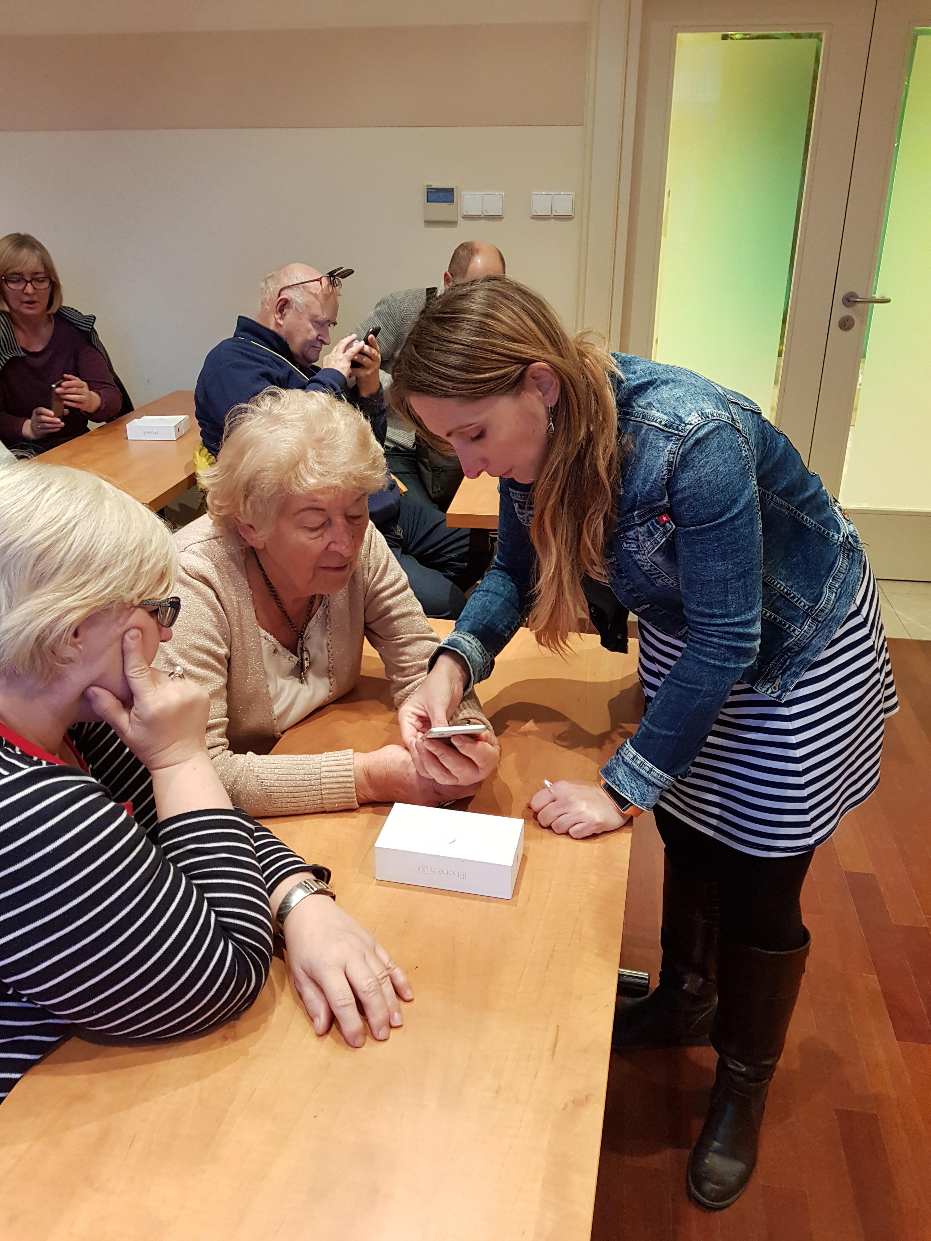 Dwie panie w starszym wieku, obie blondynki w krótszych włosach, siedzące przy stole, jedna z nich trzyma w ręku iPhone, a stojąca przy nich instruktorka wodzi jej palcem po ekranie urządzenia
