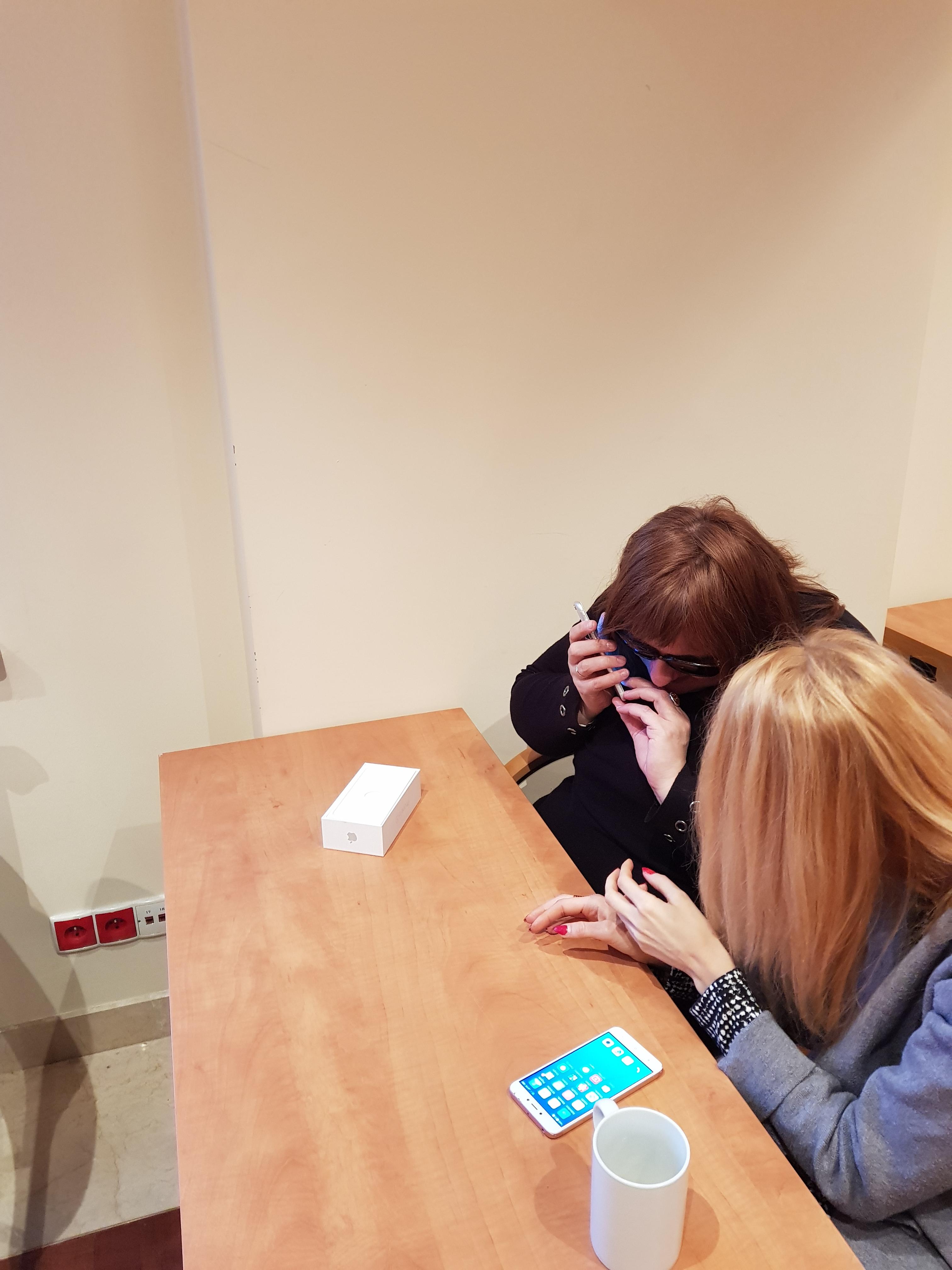 Niewidoma uczestniczka, szatynka ubrana w czarną bluzkę, siedząca przy stole testuje możliwości iPhone'a, obok zwrócona w jej kierunku druga uczestniczka w długich, prostych blond włosach