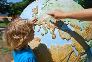 Niewidome dziecko ogląda rączkami dotykowy globus.