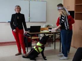 Zdjęcie - Niewidoma osoba z psem przewodnikiem i widząca uczennica z zasłoniętymi oczami próbująca czytać dotykiem